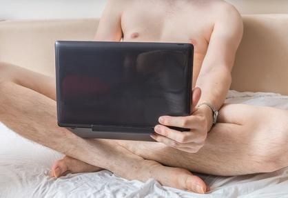 Nackter Mann onaniert im Bett vor Notebook