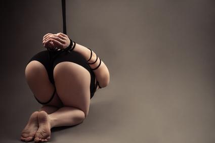Sklavin kauert am Boden, gefesselt, ihr Po ist oben