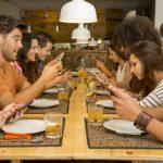 Viele junge Leute sitzen zusammen am Tisch, sind aber nicht zusammen, sondern mit ihrem Handy beschäftigt