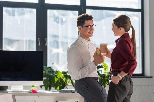 Flirt im Büro, schlanke junge Frau flirtet mit dem Kollegen