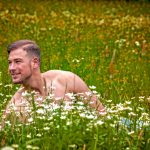 Nackter Mann am Busen der Natur, in einer Blumenwiese