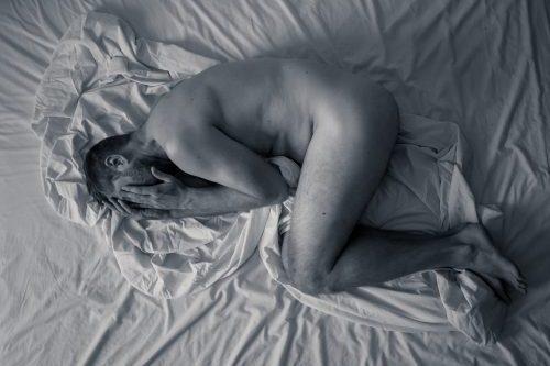 Er liegt zusammengekrümmt im Bett vor lauter Schmerz