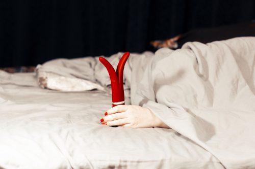 Frau im Bett mit einem Vibrator